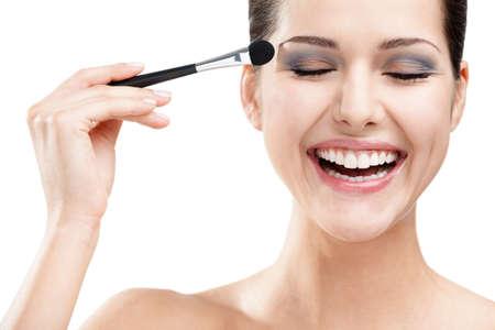 lanzamiento de bala: Mujer que aplica maquillaje con el cepillo, aislado en blanco. Procedimientos Belleza