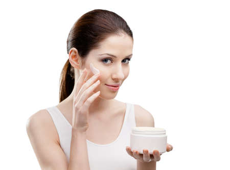 Woman applying lifting cream from container on face, isolated on white. The pursuit of beauty photo