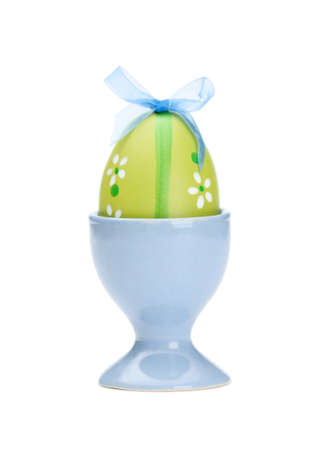 chucky: Green colored easter egg is in blue egg cup, isolated on white. Traditional symbol of the feast