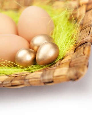 Brown and golden easter eggs are on braided plate with sisal green fibre, isolated on white Stock Photo - 18303316