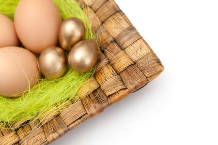 chucky: Brown and golden easter eggs are on wattled plate with sisal green fibre, isolated on white