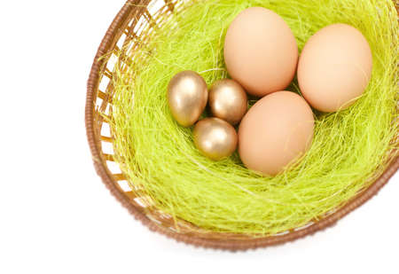 chucky: Brown and golden easter eggs are in braided basket with sisal green fibre, isolated on white