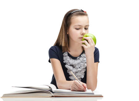 Pupil is eating a ripe apple while studying, isolated, white background photo