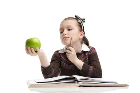 Little girl hesitates about eating a ripe green apple, isolated, white background photo