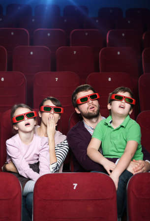 family movies: Surprised family watching a movie at the cinema Stock Photo