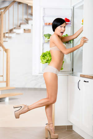 Full length of woman near the opened fridge full of vegetables and fruit. Concept of healthy and dieting food Stock Photo - 18338090