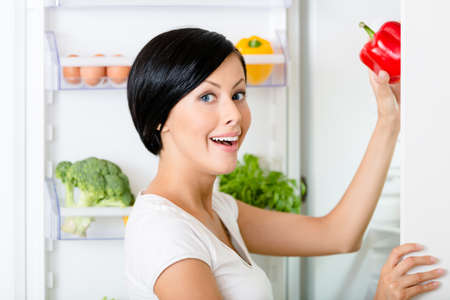 Woman takes red pepper from the opened fridge full of vegetables and fruit. Concept of healthy and dieting food Stock Photo - 18338230