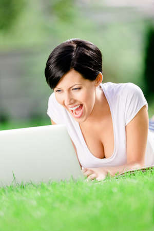 Woman lying on the green grass works at the silver laptop. Concept of the online communication photo