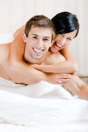 desnudo masculino: Primer plano de risa pareja que juega en la cama de la habitación. Mujer tumbada en la espalda del hombre que lo abraza