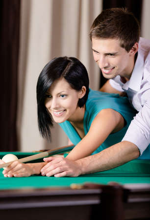Man teaching young woman to play billiards. Spending free time on gambling Stock Photo - 18338222