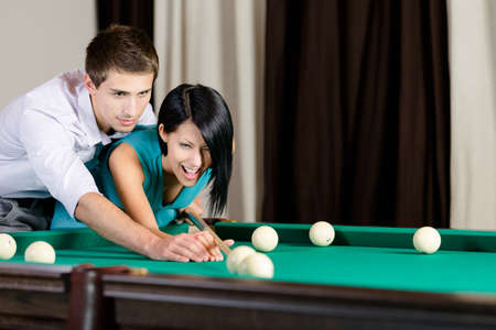 Man teaching girl to play billiard. Spending free time on gambling photo