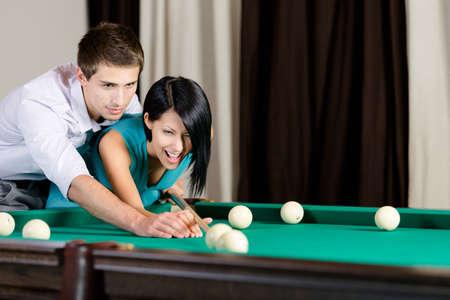 Man teaching girl to play billiard. Spending free time on gambling Stock Photo - 18338557