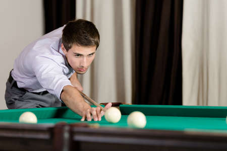 Man playing billiard. Spending free time on gambling Stock Photo - 18338303