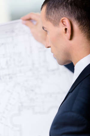 architecting: Close up of businessman with layout. Concept of successful construction