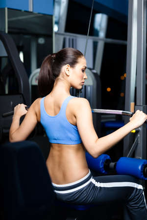 simulator: Athletic young woman works out on simulator in gym