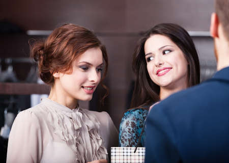Two wonderful women talk to shop assistant photo