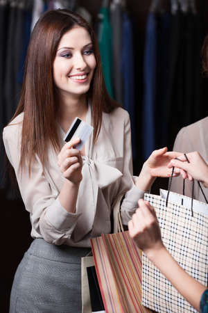Attractive woman pays with credit card for the purchase at the store photo
