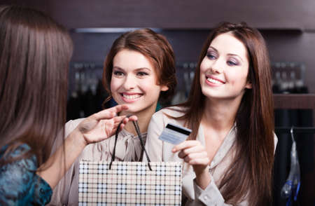 Pretty women pay with credit card and are ready to take away all purchases photo