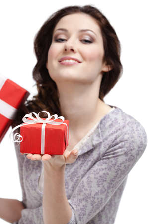 Young woman demonstrates a gift wrapped in red paper, isolated on white Stock Photo - 18574361