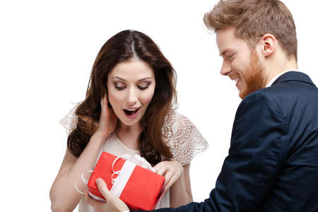 unexpected: Young man amazes his pretty girlfriend with present wrapped in red paper, isolated on white