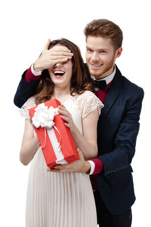 make a gift: Man closes eyes of his beautiful girlfriend to give a present in red box, isolated on white