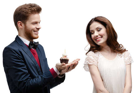 Man presents birthday cake to his girlfriend, isolated on white photo