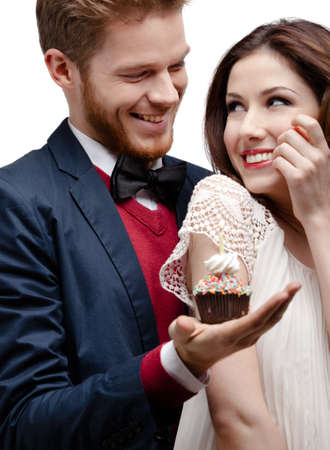 Man presents birthday cake to his pretty girlfriend who likes it very much, isolated on white photo
