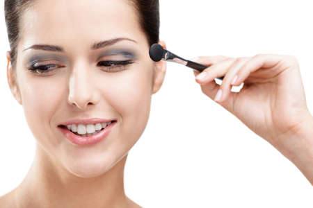 Woman applying makeup with cosmetic brush, isolated on white. Beauty procedures photo