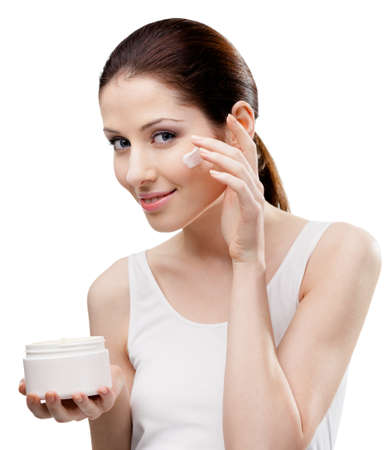 Woman putting on cream from container on face, isolated on white. The pursuit of beauty photo