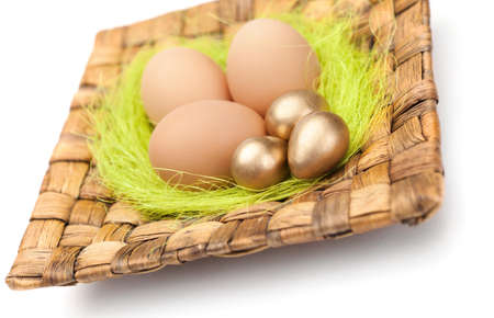 chucky: Brown and golden easter eggs are on wattled square plate with sisal green fibre, isolated on white