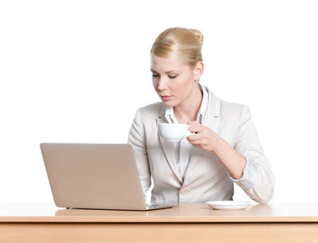Young business woman sitting at a desk with laptop, isolated Stock Photo - 18500622