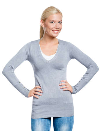 hands on hip: Girl wearing grey sweater stands with hands on the hips, isolated on white