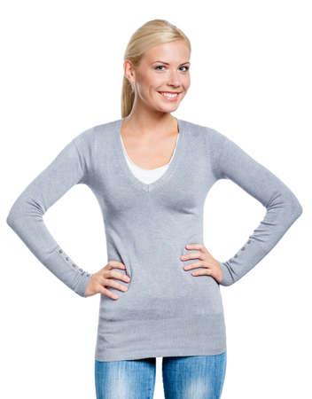 grigiastro: Ragazza che indossa un maglione grigio sta con le mani sui fianchi, isolata su bianco