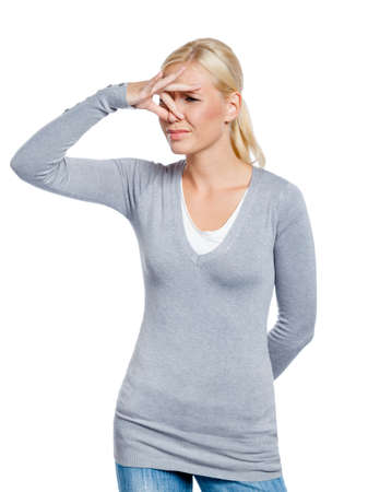 detestable: Girl covers nose with hand showing that something stinks, isolated on white