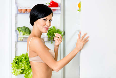 Woman eating near the opened fridge full of vegetables and fruit. Concept of healthy and dieting food photo