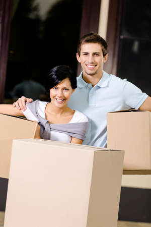 pasteboard: Happy couple carrying pasteboard containers while moving to new house Stock Photo