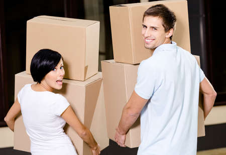 house moving: Back view of happy couple carrying pasteboard packages while moving to new house Stock Photo