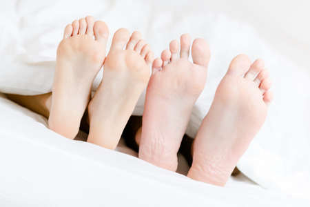 Close up of two pairs of feet of the couple next to each other in bed-room photo