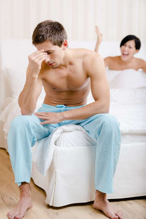 Young couple quarrels in bed. Depressed man sitting on the edge of the bed. Focus on man photo