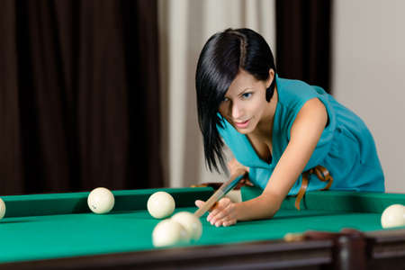 billiards tables: Young girl playing billiard. Spending free time on gambling Stock Photo