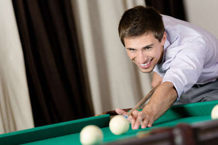 Young man playing billiard. Spending free time on gambling Stock Photo - 18500814