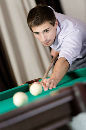 Young male playing billiard. Spending free time on gambling Stock Photo - 18500829