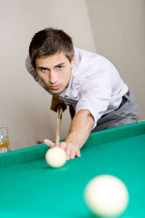Young man playing billiards. Spending free time on gambling Stock Photo - 18500734