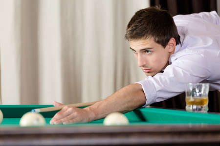 free time: Young male playing billiards. Spending free time on gambling