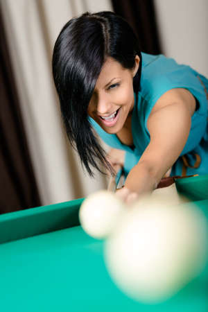 Woman playing billiards. Spending free time on gambling photo