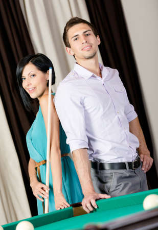 Couple standing near billiard table. Spending free time on gambling photo