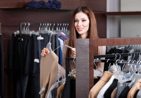 clothing tag: Pretty woman is looking for a perfect cloth in the latest fashion