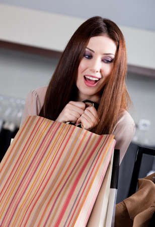 Woman doesnt want to let paper bags with gifts slip out of her hands photo