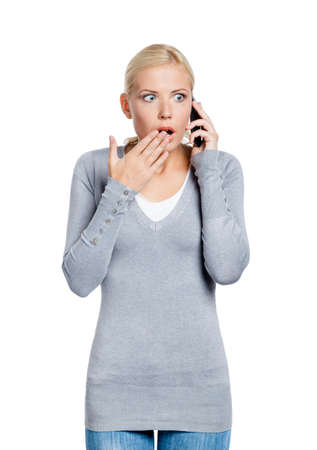adult intercourse: Speaking on phone shocked woman covers her mouth with hand, isolated on white
