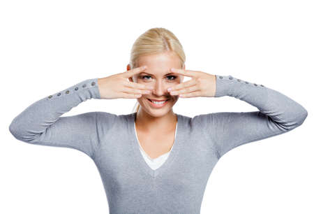 Woman covering eyes with hands look through them, isolated on white photo